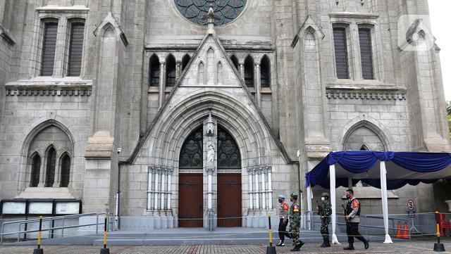 Sejumlah anggota gabungan melakukan pengamanan saat perayaan Paskah di Gereja Katedral, Jakarta, Jumat (2/4/2021). Sejumlah personel gabungan TNI-Polri disipakan untuk melakukan pengamanan di sejumlah gereja pada perayaan Paskah. (Liputan6.com/Herman Zakharia)