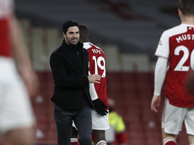Pelatih Arsenal, Mikel Arteta tersenyum saat berjalan memberi selamat kepada para pemainnya setelah pertandingan melawan Chelsea pada pertandigan lanjutan Liga Inggris di Stadion Emirates di London, Minggu (27/12/2020). Arsenal sukses mengalahkan Chelsea 3-1. (Adrian Dennis / Pool via AP)