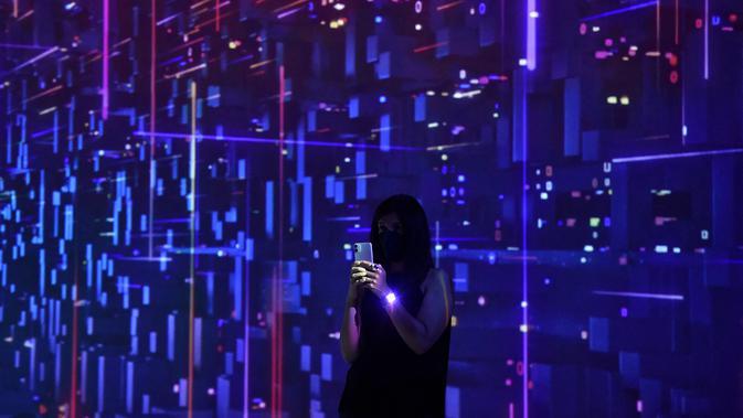Seorang wanita menggunakan ponselnya di pameran Mobile World Congress (MWC) di Barcelona (28/6/2021). MWC dianggap sebagai salah satu dari tiga acara teratas di dunia. (AFP/Pau Barrena)