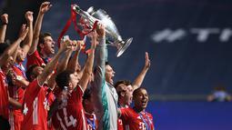 Penjaga gawang Bayern Munchen, Manuel Neuer (tengah), dan rekan satu timnya berselebrasi mengangkat trofi setelah mengalahkan PSG pada final Liga Champions di stadion Luz di Lisbon (23/8/2020). Munchen menang tipis atas PSG 1-0. (AFP/Pool/David Ramos)
