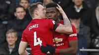 Pemain Manchester United, Phil Jones, merayakan gol yang dicetak Paul Pogba ke gawang Fulham pada laga Premier League di Stadion Craven Cottage, London, Sabtu (9/2). Fulham kalah 0-3 dari MU. (AFP/Ian Kington)