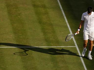 Petenis Serbia, Novak Djokovic berjalan di lapangan pada babak perempatfinal Wimbledon 2017 saat bertemu petenis Ceko, Tomas Berdych, Rabu (12/7). Djokovic memutuskan mundur setelah mengalami cedera siku saat menjalani pertandingan. (AP/Alastair Grant)