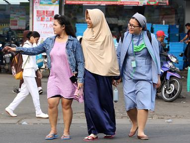 Seorang biarawati bergandeng tangan dengan wanita berkerudung saat menyeberangi jalan di kawasan Lenteng Agung, Jakarta, Rabu (18/4). Keharmonisan keduanya dapat menjadi contoh bagi masyarakat dalam menjaga kedamaian. (Liputan6.com/Immanuel Antonius)