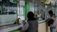 Petugas melayani warga saat transaksi di pegadaian di Jakarta, Kamis (15/6). Meningkatnya kebutuhan masyarakat jelang Lebaran membuat banyak orang menggadaikan barang berharga guna memenuhi kebutuhan yang mendesak. (Liputan6.com/Faizal Fanani)