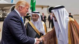 Presiden AS Donald Trump (kiri) berjabat tangan dengan Raja Arab Saudi Salman bin Abdulaziz al-Saud saat di Bandara Internasional Raja Khalid di Riyadh (20/5). (AFP/Saudi Royal Palace/Bandar Al-Jalou)