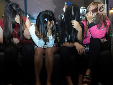 Sejumlah wanita menutupi wajahnya saat diamankan petugas Satpol PP selama razia panti pijat di BSD, Tangerang Selatan, Selasa (25/6/2019). Dalam razia tersebut puluhan wanita diamankan karena tidak bisa menunjukan kartu identitas. (merdeka.com/Arie Basuki)