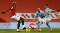 Gelandang Manchester United, Paul Pogba (kiri) dijaga dua pemain Manchester City, Riyad Mahrez (kanan) dan Kyle Walker, dalam laga lanjutan Liga Inggris 2020/21 pekan ke-12 di Old Trafford Stadium, Sabtu (12/12/2020). Manchester United bermain imbang 0-0 dengan Manchester City. (AFP/Phil Noble/Pool)