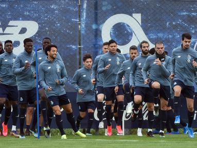 Para pemain FC Porto melakukan pemanasan saat mengikuti sesi latihan tim di tempat latihan Olival di Vila Nova de Gaia (16/2/2021). Porto akan bertanding melawan Juventus pada leg pertama babak 16 besar Liga Champions di Estadio do Dragao. (AFP/Miguel Riopa)