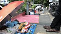 Imigran tertidur di trotoar depan Kantor UNHCR Menara Ravindo, Kebon Sirih, Jakarta, Rabu (3/7/2019). Para imigran mengaku pindah dari Rumah Detensi Imigrasi ke Kantor UNHCR lantaran tidak kunjung mendapat kabar mengenai tempat tinggal dan keputusan suaka. (merdeka.com/Iqbal Nugroho)