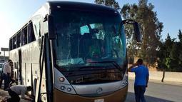 Petugas memeriksa sebuah bus wisata dan mobil yang rusak setelah ledakan bom di jalan dekat Piramida Giza, Kairo, Minggu (19/5/2019). Ledakan yang berasal dari bom pinggir jalan itu menghantam sebuah bus yang sedang melaju di Giza dan sebuah mobil di dekatnya. (AP Photo/Mohammed Salah)