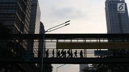 Pejalan kaki melintas di JPO Jalan Sudirman yang dipasangkan Spanduk peringatan revitalisasi, Jakarta (6/11). Ketiga JPO yang akan direvitalisasi mendapatkan penambahan lift dan CCTV. (Liputan6.com/Immanuel Antonius)