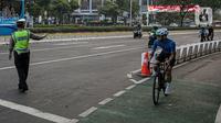 Polisi menghalau pesepeda yang berada di luar jalur di kawasan Sudirman-Thamrin, Jakarta Pusat, Rabu (2/6/2021). Sepeda road bike diperbolehkan untuk melintas di Jalan Sudirman-Thamrin pada hari kerja Senin-Jumat, namun dibatasi dari pukul 05.00-06.30 WIB. (Liputan6.com/Faizal Fanani)