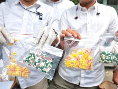 Petugas memperlihatkan barang bukti obat keras saat merilis kasus obat keras yang tidak memiliki izin edar di Mapolda Metro Jaya, Jakarta, Selasa (19/9). Polda Metro menyita 15.367 pil obat keras yang tidak memiliki izin edar. (Liputan6.com/Faizal Fanani)