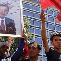 Warga membawa foto Presiden Turki, Tayyip Erdogan sambil mengibarkan bendera nasional mereka di Ankara,  Sabtu (16/7). Ratusan warga turun ke jalan untuk merayakan kegagalan kudeta militer di Turki. (REUTERS/ Tumay Berkin)