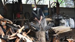 Seorang pekerja memotong kayu bakar di sebuah bengkel kerja di Damaskus, ibu kota Suriah, pada 23 November 2020. Warga Suriah mengumpulkan kayu bakar untuk menghadapi cuaca dingin. (Xinhua/Ammar Safarjalani)