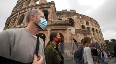 Orang-orang memakai masker untuk mencegah penyebaran COVID-19 saat mereka berjalan-jalan di dekat Colosseum, di Roma pada Sabtu (3/10/2020). Masker wajah harus dipakai setiap saat di luar rumah di ibu kota Italia Roma dan wilayah sekitar Lazio mulai Sabtu, 3 Oktober. (AP Photo/Andrew Medichini)
