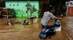 Warga melintasi banjir yang melanda kawasan bantaran kali Cisadane, Tangerang, Jumat (26/4). Banjir kiriman setinggi 2 meter sempat melanda kawasan akibat curah hujan yang tinggi di bogor membuat derasnya air mengalir jauh sampai ke tempat ini. (Liputan6.com/Johan Tallo)