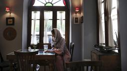 Seorang wanita menghabiskan sore di sebuah kafe di pusat kota Teheran, Iran (10/8/2019). Teheran adalah kota yang sarat dengan kehidupan yang terletak di kaki pegunungan Alborz dengan jaringan jalan tol yang tak tertandingi di Asia Barat. (AP Photo/Vahid Salemi)