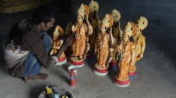 Seorang seniman India mewarnai patung dewa Hindu Rama di sebuah lokakarya di Hyderabad, India (15/3). Umat Hindu India akan merayakan festival Rama Navami yang jatuh pada tanggal 25 Maret. (AFP/Noah Seelam)