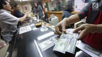 Teller menghitung mata uang dolar di Jakarta, Jumat (2/2). Deputi Gubernur BI Senior Mirza Adityaswara mengatakan, bahkan sebelum fluktuasi yang terjadi beberapa hari ini, rupiah sudah undervalue. (Liputan6.com/Angga Yuniar)