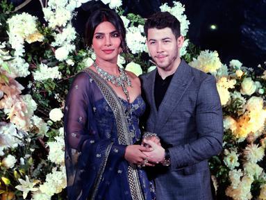 Pasangan aktris Bollywood Priyanka Chopra dan musisi Nick Jonas berpose untuk resepsi pernikahan mereka di Mumbai, India, Rabu (19/12). Resepsi kedua Priyanka Chopra dan Nick Jonas hanya mengundang kerabat dan teman dekat. (AP/Rajanish Kakade)