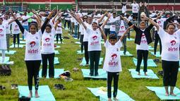 Ratusan warga melakukan gerakan yoga saat mengikuti sesi yoga massal di Stadion Afraha di Nakuru, Kenya (15/6/2019). Acara yoga massal ini untuk memperingati Hari Yoga Internasional. (AFP Photo/Suleiman Mbatiah)
