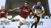 Gelandang AC Milan, Hakan Calhanoglu, melepaskan tendangan ke arah gawang Atalanta pada laga lanjutan Serie A di Stadion San Siro, Sabtu (25/7/2020) dini hari WIB. AC Milan bermain imbang 1-1 atas Atalanta. (Spada/LaPresse via AP)