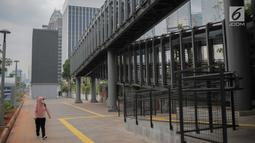 Pejalan kaki melintas di dekat JPO di Jalan Sudirman, Jakarta, Rabu (28/8/2019). Pemprov DKI Jakarta akan membangun 15 JPO berkonsep modern atau futuristik pada 2020. Tujuannya untuk memfasilitasi pejalan kaki agar nyaman mengakses transportasi publik. (Liputan6.com/Faizal Fanani)