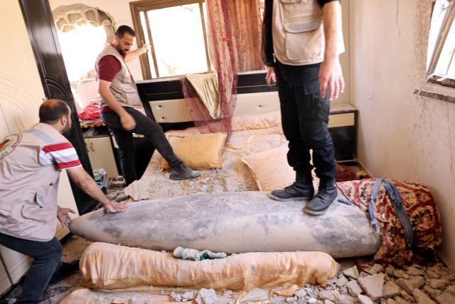 Pakar peledak Hamas saat sedang memeriksa rudal Israel yang tidak meledak setelah menghantam di sebuah rumah di Khan Yunis, Jalur Gaza selatan (20/5/2021). Dari sekian banyak rudal Israel yang meluncur dan meledak di Gaza, ada beberapa rudal yang tak meledak usai menghantam sasaran. (AFP/Said Khatib