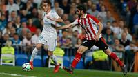 Pemain Real Madrid, Lucas Vazquez berebut bola dengan pemain Athletic Bilbao, Raul Garcia pada pekan ke-33 La Liga di Santiago Bernabeu, Rabu (18/4). Real Madrid kembali meraih hasil minor usai bermain imbang 1-1 lawan Atletico Bilbao. (AP/Francisco Seco)