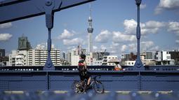 Seorang pria dengan sepeda berhenti di jembatan di Tokyo, Senin (28/9/2020). Ibukota Jepang mengonfirmasi lebih dari 70 kasus virus corona pada hari Senin. (AP Photo / Eugene Hoshiko)
