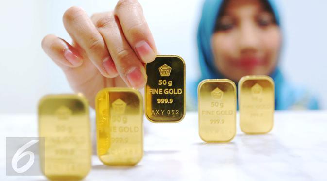 Pegawai menunjukan emas batangan di Jakarta, Senin (10/10). Di awal pekan ini, harga emas PT Aneka Tambang Tbk (ANTAM) tetap bertahan di Rp 599 ribu per gram. (Liputan6.com/Angga Yuniar)