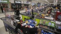 Jonata Anjo berbaring di kasir di supermarket Carrefour selama protes terhadap pembunuhan pria kulit hitam Joao Alberto Silveira Freitas di supermarket Carrefour, pada Hari Kesadaran Kulit Hitam Nasional Brasil di Rio de Janeiro, Brasil (20/11/2020). (AP Photo/Bruna Prado)