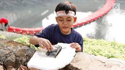 Seorang anak bermain di pinggir sungai buatan di kawasan Kuningan, Jakarta, Senin (13/8). Meskipun tidak baik bagi kesehatan dan keselamatan mereka, anak-anak tersebut tempat bermain di sungai tersebut. (Liputan6.com/Immanuel Antonius)
