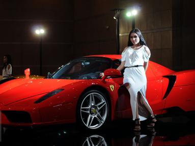 Seorang model bergaya di sisi mobil Ferrari yang dipamerkan di Indonesia International Motor Show 2015 di JI Expo Kemayoran Jakarta, Rabu (19/8/2015). Puluhan merek kendaraan ternama ikut ambil bagian dalam IIMS 2015. (Liputan6.com/Helmi Fithriansyah)