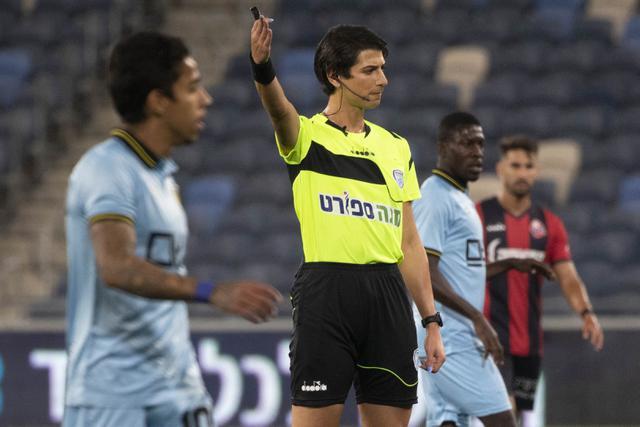 Wasit Sapir Berman memimpin pertandingan Liga Premier Israel antara Hapoel Haifa vs Beitar Jerusalem di kota Haifa, Senin (3/5/2021). Wasit sepak bola transgender pertama Israel turun ke lapangan untuk pertama kalinya sejak tampil di depan umum sebagai seorang wanita.  (AP Photo/Sebastian Scheiner)