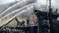 Para pekerja mencoba membantu memadamkan api di kapal nelayan di Pelabuhan Benoa, Denpasar, Bali, Senin (9/7). Hingga kini pemilik kapal masih belum bisa dimintai keterangan. (SONNY TUMBELAKA/AFP)