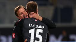Pelatih Werder Bremen, Florian Kohfeldt, memeluk Sebastian Langkamp setelah timnya berhasil bertahan di kompetisi Bundesliga usai menahan imbang Heidenheim 1846 di laga play-off leg kedua, Selasa (7/7/2020) dini hari WIB. Bremen bermain imbang 2-2 atas Heidenheim. (AFP/Kai Pfaffenbach/pool)