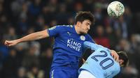 Bek Leicester City Harry Maguire berebut bola dengan gelandang Manchester City, Bernardo Silva pada perempat final Piala Liga Inggris di King Power Stadium, Selasa (19/12). Manchester City melaju ke semifinal usai menang dengan skor 4-3. (Paul ELLIS/AFP)