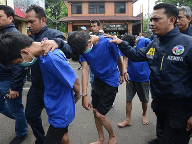 Tiga tersangka perkara kasus pengedaran narkoba jenis shabu dan psikotopika golongan IV serta obat daftar G pada sebuah sekolah berinisial AN, DL, CP dibawa petugas di Polres Jakarta Barat, Selasa (15/1). (Merdeka.com/Imam Buhori)