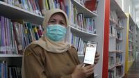 Kepala Dinas Perpustakaan dan Kearsipan Kabupaten Garut, Lisnawati tengah menunjukan penggunaan aplikasi online i-Bagendit bagi masyarakat di masa pandemi. (Liputan6.com/Jayadi Supriadin)