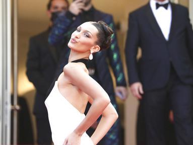 Supermodel Bella Hadid berpose untuk fotografer setibanya di pemutaran perdana film 'Annette' dan upacara pembukaan Festival Film Cannes ke-74 di Prancis selatan, Selasa (6/7/2021). Model berusia 24 tahun itu tampil memukau dengan gaun hitam putih Jean Paul Gaultier. (Vianney Le Caer/Invision/AP)
