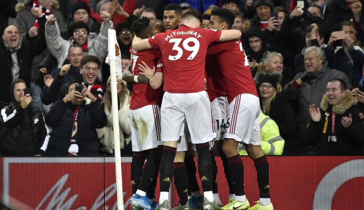 Penyerang Manchester United, Marcus Rashford (tengah) berselebrasi dengan rekan-rekannya usai mencetak gol pembuka ke gawang Tottenham Hotspur pada pertandingan lanjutan Liga Inggris di Old Trafford, Rabu (4/12/2019). MU menang tipis atas Tottenham 2-1. (AP Photo/Rui Vieira)