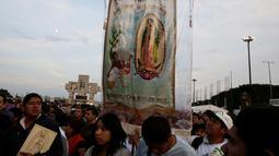 Peziarah membawa gambar Bunda dari Guadalupe saat mereka tiba di kawasan Basilika Guadalupe di Mexico City, Meksiko (11/12). Ritual ziarah ini dilakukan setiap tahunnya untuk menghormati Bunda dari Guadalupe. (Reuters/Henry Romero)