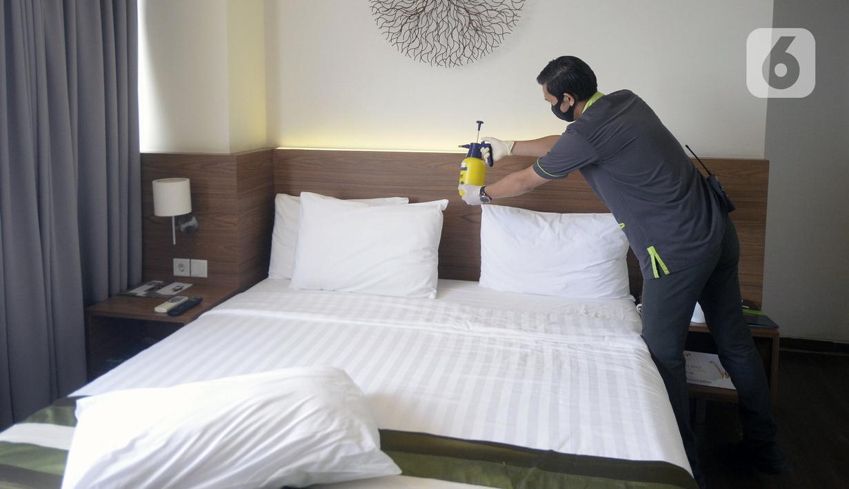 Pegawai melakukan penyemprotan disinfektan di kamar Hotel Grand Whiz Poins Simatupang, Jakarta, Kamis (16/4/2020). Hotel ini menyediakan paket isolasi mandiri untuk mendukung program pembatasan sosial berskala besar (PSBB) di tengah pandemi virus corona COVID-19. (merdeka.com/Dwi Narwoko)