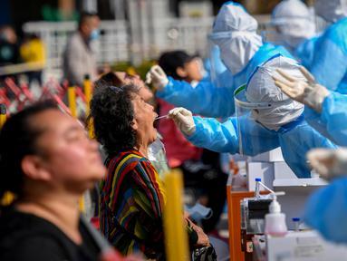 Petugas medis mengambil sampel warga saat tes COVID-19 di Qingdao, China, Senin (12/10/2020). Lebih dari 9 juta orang yang tinggal di kota Qingdao menjalani tes COVID-19 secara massal setelah kasus baru muncul terkait dengan rumah sakit yang merawat pasien terinfeksi dari luar negeri. (STR/AFP)