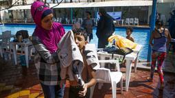 Seorang ibu menyeka wajah anak laki-lakinya yang menderita autisme setelah berpartisipasi dalam sesi terapi renang di Beit Lahia di Jalur Gaza utara, Palestina  (5/8/2019). (AFP Photo/Mohammed Abed)