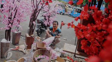 Pengrajin Pohon Hias Imlek menyelesaikan pekerjaannya di kawasan Glodok, Jakarta, Kamis (21/1/2016). Pembeli dapat memesan sesuai keinginan dengan kisaran harga 50.000 - 3.500.000 rupiah. (Liputan6.com/Gempur M Surya)