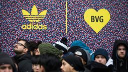 Calon pembeli mengantre untuk mendapatkan sepatu Adidas/BVG (Berlin Transport) di luar toko Overkill di Berlin, Jerman, Selasa (16/1). Sepatu tersebut dijual dengan harga 180 Euro atau sekitar Rp 2,95 juta. (AFP PHOTO / Odd ANDERSEN)