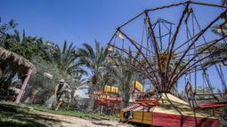 Seorang pekerja mengenakan masker menyiram tanah dan kursi komedi putar di kebun binatang lokal Palestina di Rafah di Jalur Gaza selatan (26/5/2020). Kebun binatang itu ditutup selama liburan Idul Fitri karena pandemi virus coronavirus COVID-19. (AFP/Said Khatib)